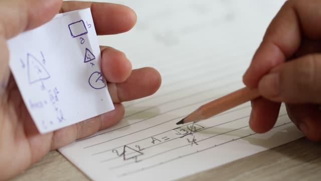 studente che usa il foglio matematico della formula per imbrogliare il test. mano dello studente universitario che tiene la matita facendo domanda matematica in esame e barando in prova con un pezzo di carta di risposta in mano. - esame università video stock e b–roll