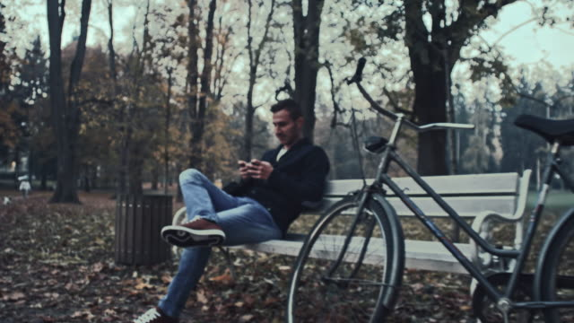 Student using his smartphone while sitting in the park video