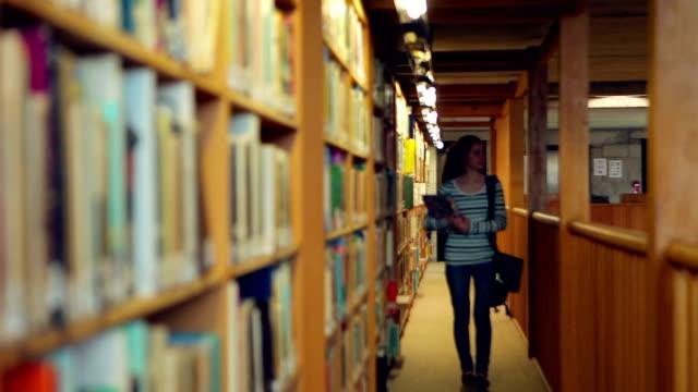stockvideo's en b-roll-footage met student walking through the library - boekenkast