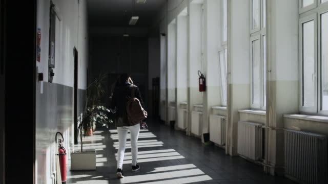 A student walks down the empty hall of a school