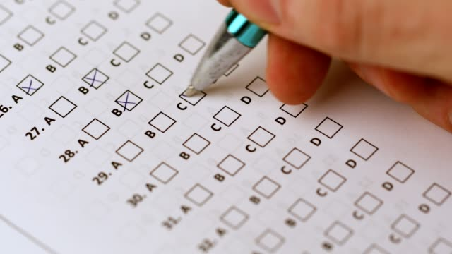 student with pen filling in answer sheet