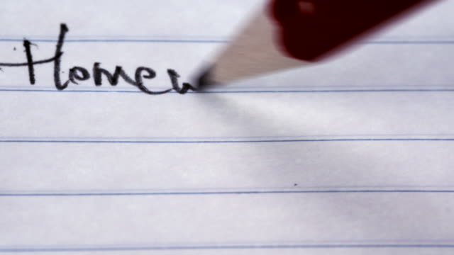 Um aluno escreve a palavra 'Lição' em um nota de papel pautado - vídeo