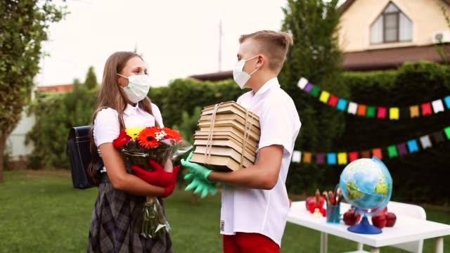 studenter en pojke och en flicka i medicinska masker och handskar talar - människorygg bildbanksvideor och videomaterial från bakom kulisserna