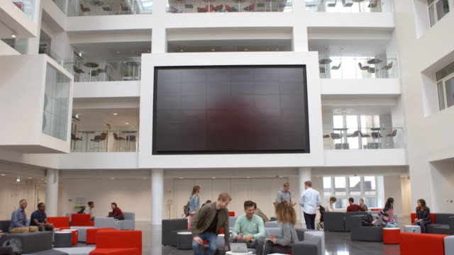 Students and AV screen in atrium at a university, tilt shot Students and AV screen in atrium at a university, tilt shot lobby stock videos & royalty-free footage