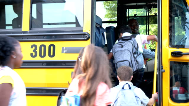 Students and teacher boarding school bus A multi-ethnic group of six middle school children, 11 to 13 years old, and their Hispanic teacher boarding a yellow school bus. The bus driver, an African American man wearing a reflective clothing, opens the door and the students enter one at a time. The boy wearing eyeglasses has down syndrome. school buses stock videos & royalty-free footage