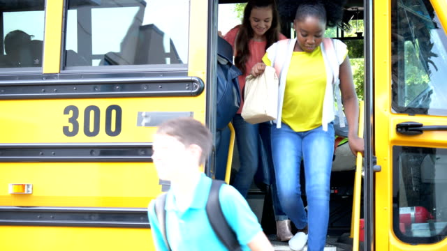 Students and teacher exit school bus A multi-ethnic group of six middle school children, 11 to 13 years old, and their Hispanic teacher exiting a yellow school bus. The bus driver, an African American man wearing a reflective clothing, opens the door and the students exit one at a time. The boy wearing eyeglasses has down syndrome. middle school teacher stock videos & royalty-free footage