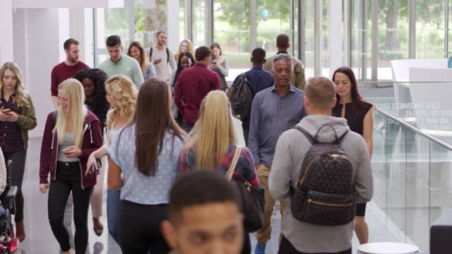 Students and teachers walk in foyer of a modern university, shot on R3D video
