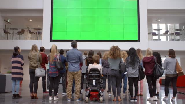 stockvideo's en b-roll-footage met studenten juichen een groot scherm in de universiteits foyer, terug te bekijken - bewondering