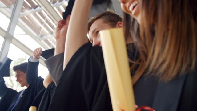 Alumnos en ceremonia de graduación lanzando los sombreros al aire - vídeo