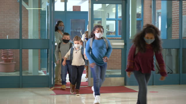 vídeos de stock, filmes e b-roll de alunos voltam à escola durante o covid-19, usando máscaras - criança