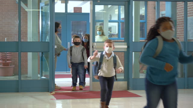 Students back to school during covid-19, wearing masks A multi-ethnic group of elementary school students returning to school wearing face masks during the covid-19 pandemic. They are walking in through the front door single file. Teachers wearing masks and gloves are making sure they follow the rules and social distance. The children are 7 to 10 years old. school building stock videos & royalty-free footage
