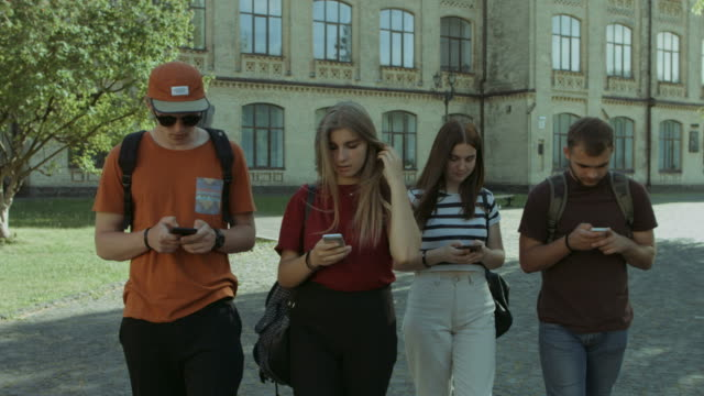 students busy with cellphones walking in campus - teenagers stock videos & royalty-free footage