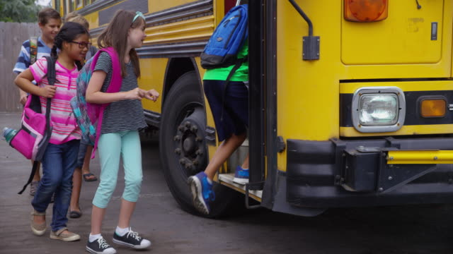 Students get onto school bus, slow motion video