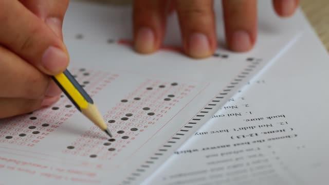 studenti a mano che fanno gli esami, scrivono la sala d'esame con matita in possesso di matita su forma ottica di prova standardizzata con risposte e foglio di carta inglese sulla sedia da scrivania a fila facendo l'esame finale in aula. - esame università video stock e b–roll