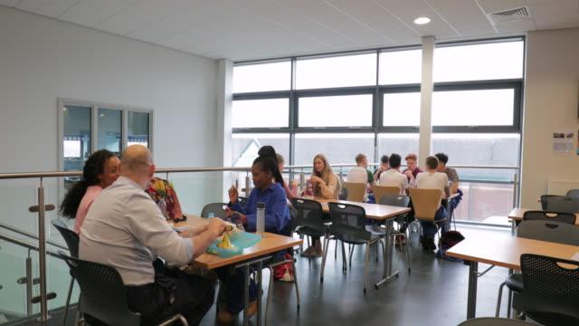 vídeos de stock e filmes b-roll de students having lunch with friends - cantina
