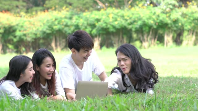students making group reports to send instructors. people meeting team and using laptop computer in the park outdoors. concept of education, together, teamwork, learning, knowledge and research. - compagni scuola video stock e b–roll