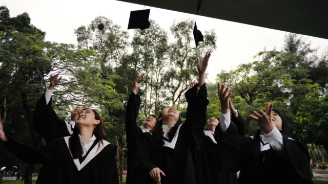 Students on graduation ceremony throwing caps in the air