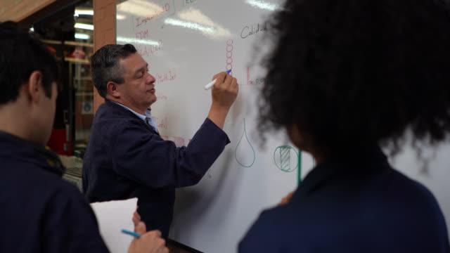 schüler achten darauf, während lehrer etwas auf whiteboard erklärt, während andere schüler an ihrem projekt während einer holzwerkstatt arbeiten - nachhilfelehrer stock-videos und b-roll-filmmaterial