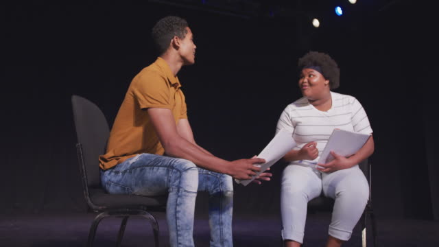 Students preparing before a high school performance in an empty school theater Front view of a mixed race high school teenage boy and African American teenage girl sitting on chairs in an empty school theater preparing before a performance, holding scripts and rehearsing together, in slow motion performer stock videos & royalty-free footage