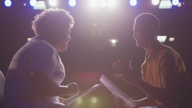 Students preparing before a high school performance in an empty school theater Side view close up of a mixed race high school teenage boy and African American teenage girl sitting on chairs in an empty school theatre preparing before a performance, holding scripts and rehearsing together, and high fiving, backlit by stage lights, in slow motion performer stock videos & royalty-free footage