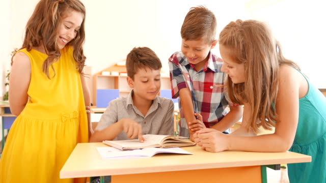 Students reading a book in classroom video