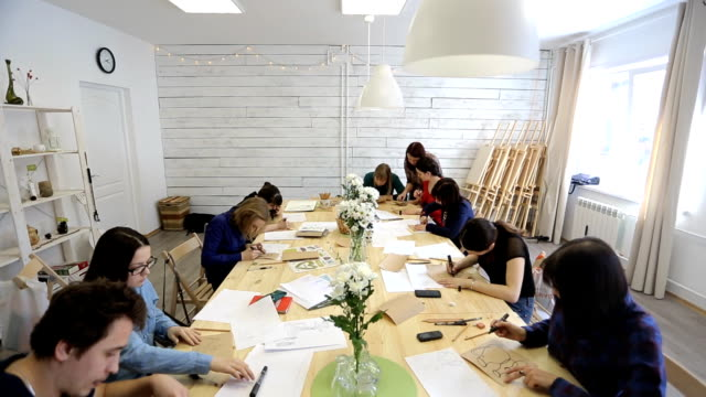 Students sit around long squared wooden table and draw sketches ビデオ