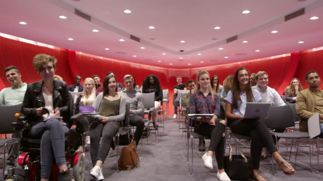 Students sit facing camera in a modern university classroom, shot on R3D video