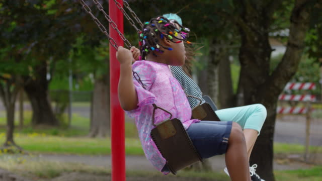 Students swing on school playground Students swing on school playground, slow motion swinging stock videos & royalty-free footage