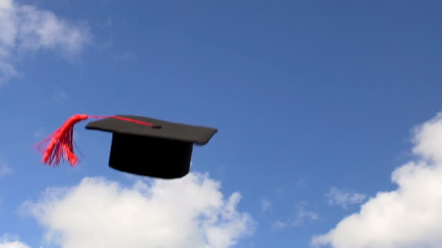 students throwing mortarboards with tassels in blue sky, celebrating graduation - graduation cap stock videos & royalty-free footage