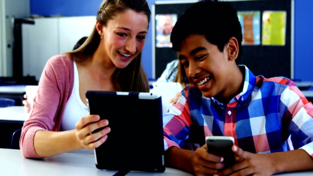 Students using digital tablet and mobile phone in classroom video