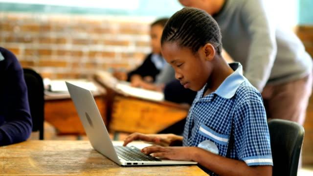 elever som använder laptop och digitala tablett i klassrummet 4k - digital reading child bildbanksvideor och videomaterial från bakom kulisserna