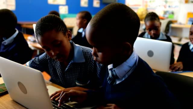 stockvideo's en b-roll-footage met studenten met behulp van de laptop in de klas 4k - schooljongen