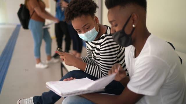 vídeos de stock, filmes e b-roll de alunos que usam bloco de notas para estudar juntos no pátio da escola - estudante