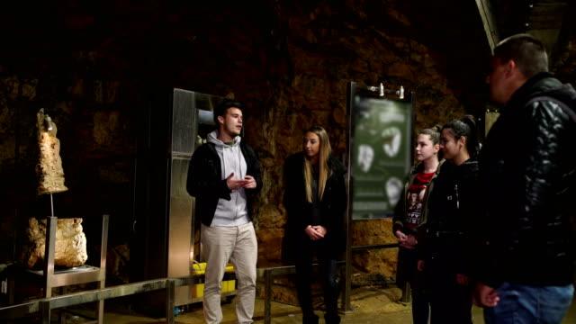 学生は古代の洞窟を訪問し、何か新しいことを学びます - 記念建造物点の映像素材/bロール