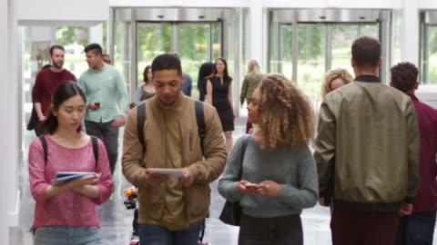 vídeos y material grabado en eventos de stock de los estudiantes que caminan por el vestíbulo de una universidad moderna, dispararon sobre r3d - estudiante