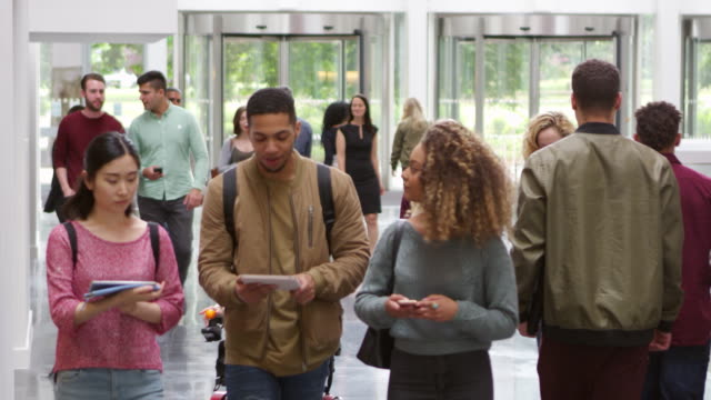 Students walking through the foyer of a modern university, shot on R3D video