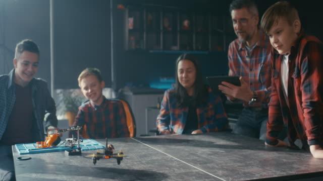 vídeos de stock, filmes e b-roll de estudantes assistindo drone voador em sala de aula - quadricóptero