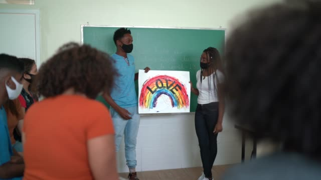 vídeos de stock, filmes e b-roll de estudantes usando máscara facial fazendo uma apresentação sobre direitos lgbtqi - lgbt