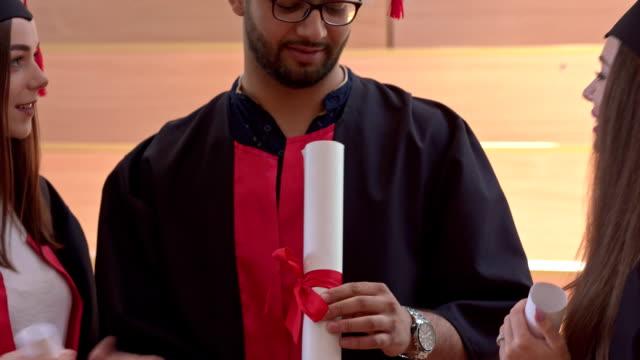 vídeos y material grabado en eventos de stock de estudiantes usando graduación vestido hablando y bromeando. - baile de estudiantes de secundaria