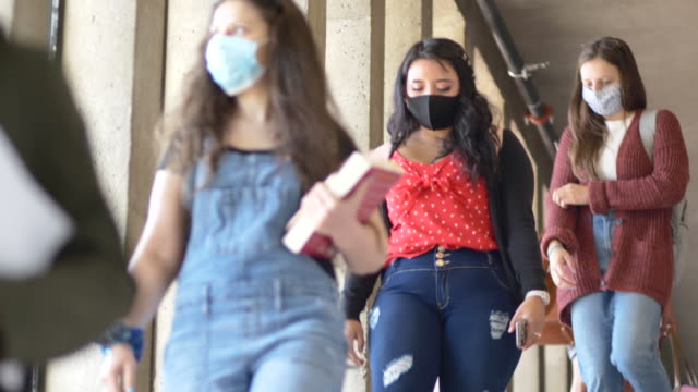 Students wearing masks on campus College students wearing protective face coverings and keeping a safe distance while on campus due to new COVID-19 regulations. campus stock videos & royalty-free footage