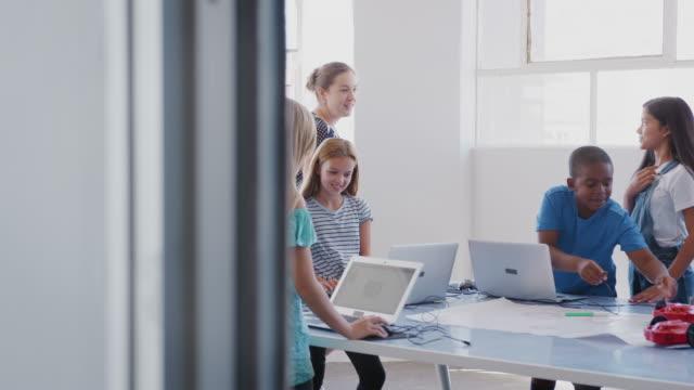 vídeos y material grabado en eventos de stock de estudiantes con profesora en clase de codificación de computadoras después de la escuela aprendiendo a programar vehículo robot - escuela media