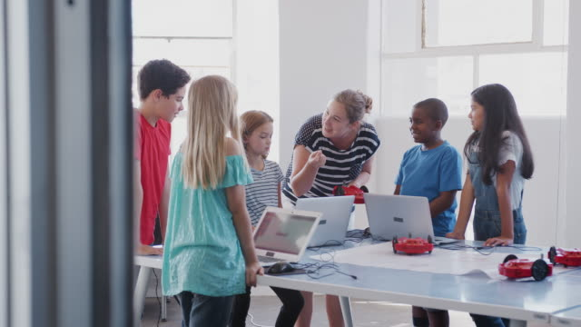 Students With Female Teacher In After School Computer Coding Class Learning To Program Robot Vehicle Dolly shot of students with female teacher in after school computer coding class learning to program robot vehicles - shot in slow motion middle school teacher stock videos & royalty-free footage