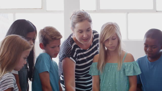 Students With Female Teacher In Class Collaborating On Project Together Group of students with female teacher collaborating on project together - shot in slow motion middle school teacher stock videos & royalty-free footage