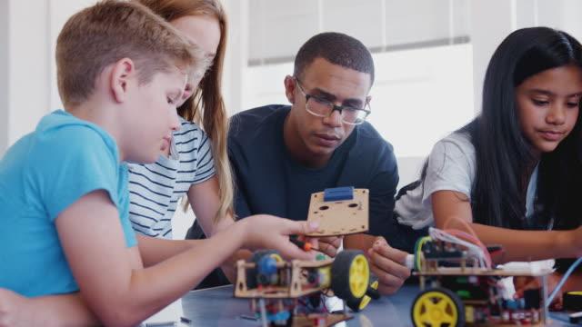 vídeos y material grabado en eventos de stock de estudiantes con profesor masculino en clase de codificación de computadoras después de la escuela aprendiendo a construir vehículo robot - escuela media