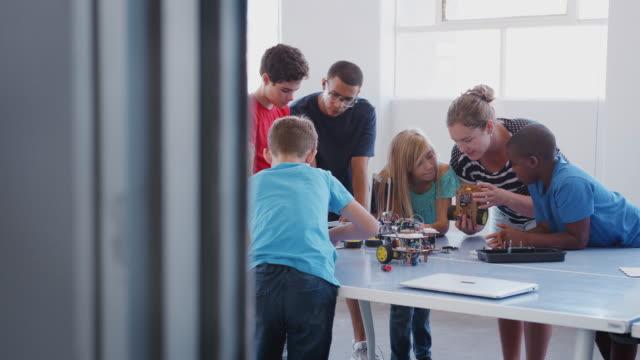 vídeos y material grabado en eventos de stock de estudiantes con maestros en clase de codificación informática después de la escuela aprendiendo a programar vehículo robot - escuela media