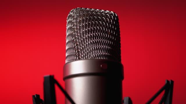 vidéos et rushes de le microphone de condensateur de studio tourne sur le fond rouge - podcasting
