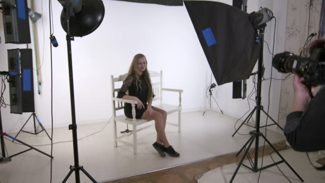 Studio photography. Female photographer works with blonde young model in studio Studio photography. Female photographer works with blonde young model in studio. Woman photographing teen girl on white background. Backstage shot during indoor photoshoot. photo shoot stock videos & royalty-free footage