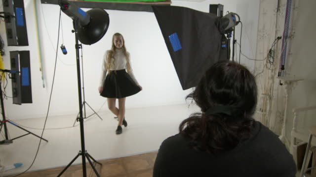 Studio photography. Teen girl poses for photographer in photo studio Studio photography. Teen girl poses for photographer in photo studio. Woman photographing young blonde model on white background. Backstage shot during indoor photoshoot. photo shoot stock videos & royalty-free footage
