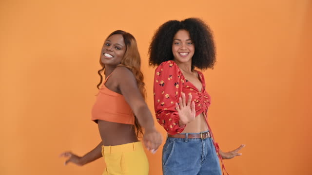 Studio portrait of casual young black female friends dancing Black and mixed race women in their 20s with medium-length and long hair wearing casual clothing, standing side by side and smiling at camera then dancing. back to back stock videos & royalty-free footage