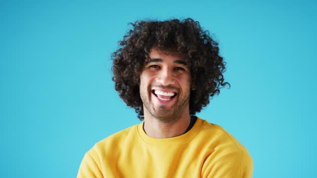 studioportrait von selbstbewusst lächelnden jungen mann lachen vor blauem hintergrund - farbiger hintergrund stock-videos und b-roll-filmmaterial